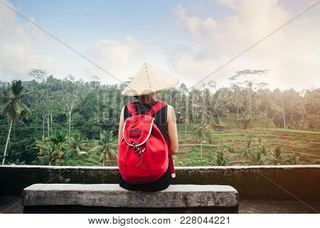 Young Lady With Traditional Asian Hat With Backpack Sitting Near Rice Field, Intentional Sun Glare