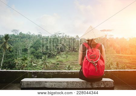 Young Lady With Traditional Asian Hat With Backpack And Sitting At Rice Field, Intentional Sun Glare