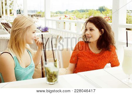 Portrait Of Two Pretty Modern Real Girl Friends In Cafe Open Air Interior Drinking And Talking, Havi