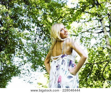 Happy Blond Young Woman In Green Spring Park Smiling, Floral Happy Close Up