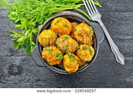 Meatballs With Tomato Sauce In A Brazier With Parsley, Dill, Fork On A Black Wooden Board Background