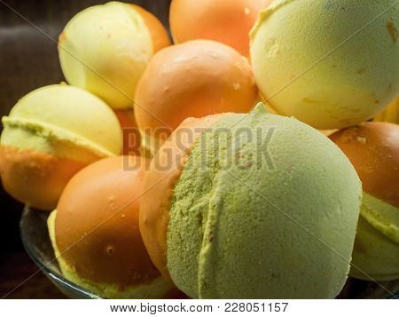 Dollops Of Two-flavored Ice Cream Served On A Glass Bowl. A Closeup View.