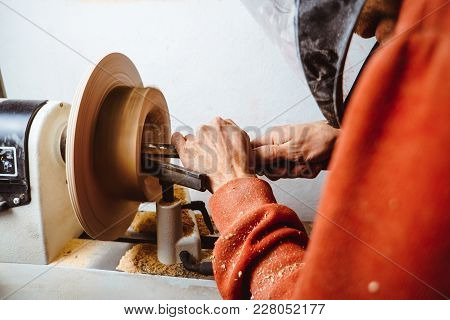 The Worker Turns The Wood On A Lathe In His Workshop