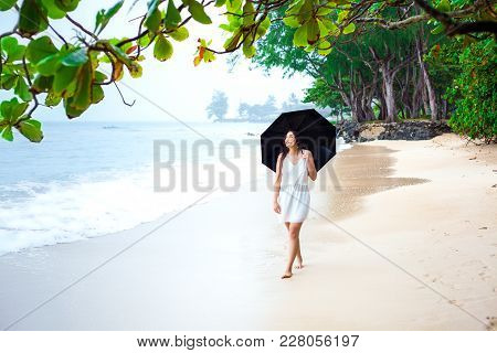 Young Biracial Asian Caucasian Woman Or Teen Walking On Beach Holding Umbrella On Overcast Rainy Day