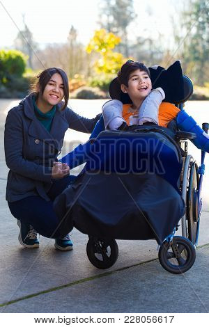 Smiling Eleven Year Old Disabled Boy In Wheelchair Outdoors With His Sister Or Caregiver