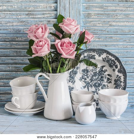 Pink Roses In A White Enameled Pitcher, Vintage Crockery On Blue Wooden Rustic Background. Kitchen S