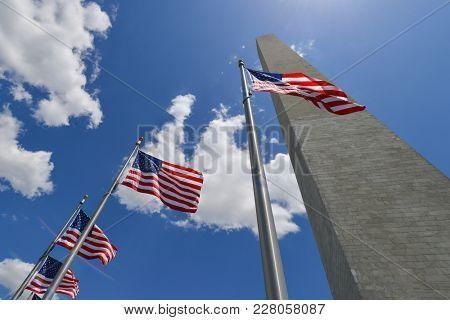 Washington Monument with waving United States National Flags on flagpoles - Washington DC United States