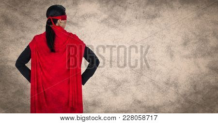 Digital composite of Back of business woman superhero with hands on hips against cream background with grunge overlay