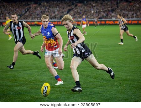 MELBOURNE - AUGUST 20 : Ben Sinclair (front) attacks the ball during Collingwood's  win over Brisbane - August 20, 2011 in Melbourne, Australia.