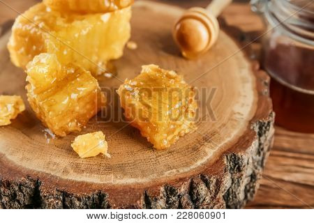 Sweet honeycombs and dipper on wooden stub, closeup