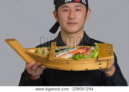 Asian cook holding Japanese assorted sushi food boat wearing black bandana with Chinese word translation ( Victory )