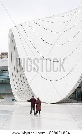 Baku, Azerbaijan - January 01, 2018: Old couple walks on the teritory of Heydar Aliev Center, Baku, Azerbaijan