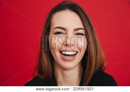 Photo closeup of beautiful adult girl 20s with long brown hair smiling with perfect teeth and looking on camera isolated over red background poster