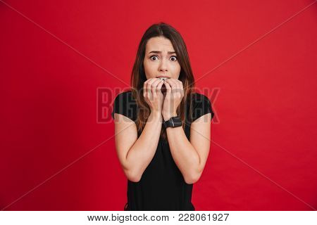 Photo of caucasian woman 20s in black t-shirt biting nails and feeling unsafe and frightened isolated over red background