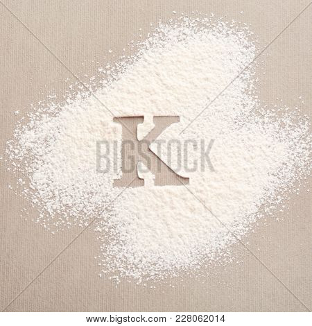 Silhouette of letter K on scattered flour