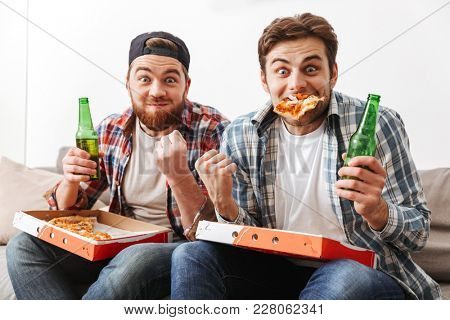 Two emotional bachelors having fun and rejoicing win of football team with eating pizza and drinking beer at home