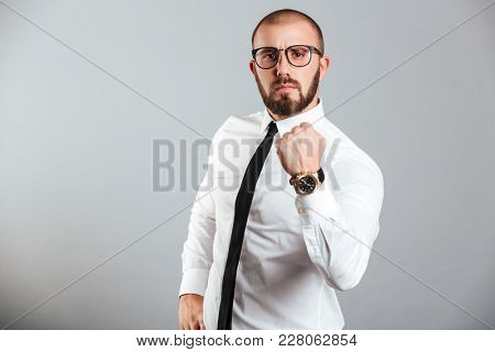 Photo of young businessman in white shirt and eyeglasses firmly showing fist meaning strength or fortitude isolated over gray background