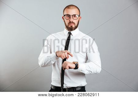 Portrait of a serious businessman pointing finger at his wristwatch isolated over gray background