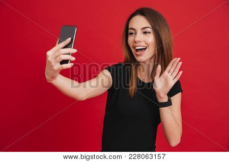 Joyous photo of woman in black t-shirt with long auburn hair taking selfie and waving hand on her smartphone isolated over red background