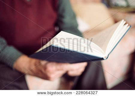 closeup of an old caucasian man reading a book sitting in a comfortable couch
