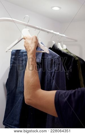 closeup of a young caucasian man hanging or unhanging a pair of jeans on the rack of a closet