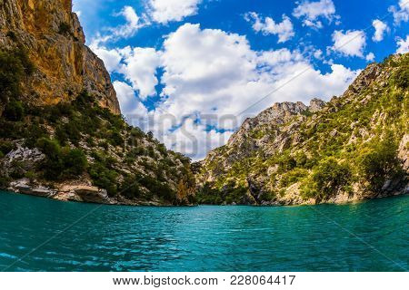 The river flow between the sheer cliffs of Verdon Canyon. Fascinating journey through the azure waters. The Verdon River, Provence Alps, France. Concept of ecological and active tourism