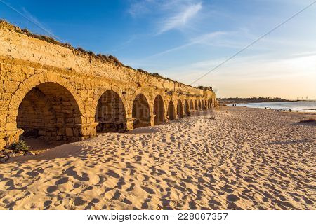 The aqueduct, built in the early Byzantine period. Fantastic sunset on the Mediterranean coast in Caesarea. sandy beach is trampled by tourists. Concept of active, ecological and historical tourism