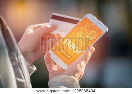 Smartphone with modern fortunetelling application on screen and hand with a credit card ready to pay for access to the application. Pay for divination concept