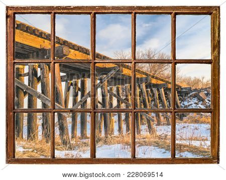 old railroad trestle as seen through vintage sash window with dirty glass