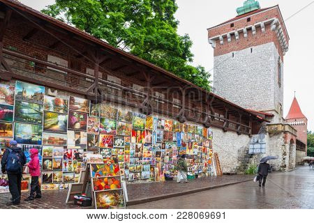 KRAKOW, POLAND - JUNE 28, 2013: Oil paints gallery on the city walls of Krakow old town, Poland. This famous street gallery is located on the city walls at St. Florian Gate, the focal point of Krakow.