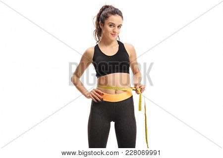 Teenage girl measuring her waist with a measuring tape isolated on white background