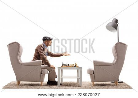 Elderly man playing a game of chess and arguing with an empty armchair isolated on white background