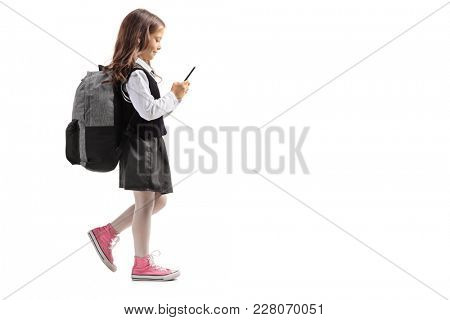 Full length profile shot of a little schoolgirl walking and using a phone isolated on white background