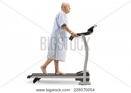 Full length profile shot of an elderly patient walking on a treadmill isolated on white background