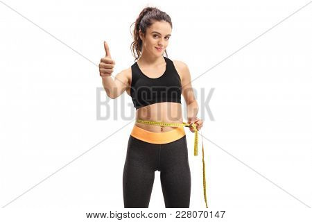 Young girl measuring her waist with a measuring tape and making a thumb up sign isolated on white background