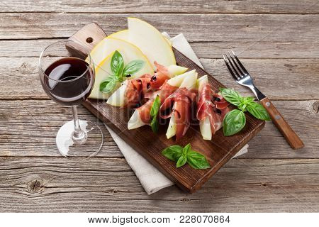 Fresh melon with prosciutto and basil. Antipasti and red wine. On wooden table