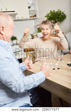Senior celebrating victory in board game match and having fun