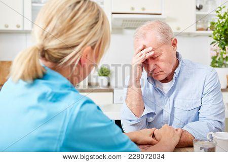 Nurse comforts senior man with dementia and depression