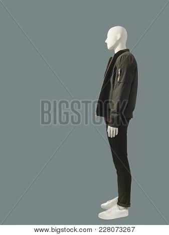 Full-length Man Mannequin Dressed In Casual Clothes Over Green Background. No Brand Names Or Copyrig