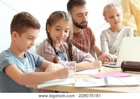 Children doing homework with teacher in classroom at school