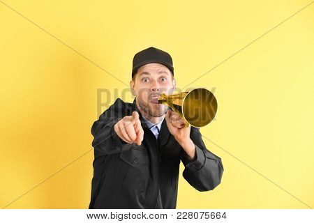 Male security guard with megaphone on color background