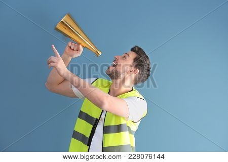 Worker with megaphone on color background