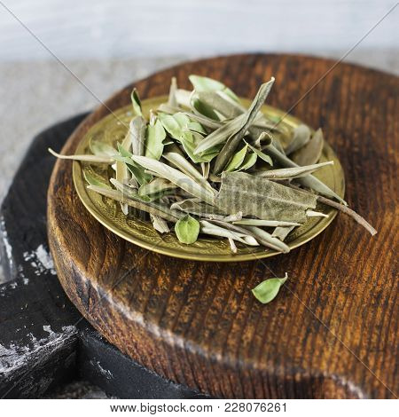 Dry Olive Bay Leaves In A Copper Plate On A Wooden Board