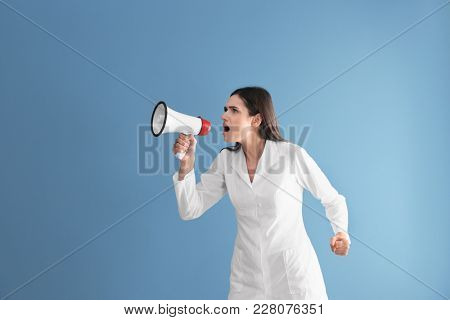 Female doctor with megaphone on color background