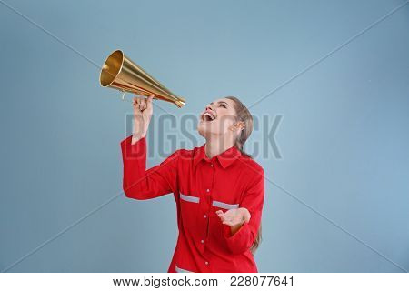Young female emergency doctor with megaphone on color background