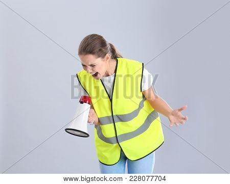 Young woman in reflective vest shouting into megaphone on grey background