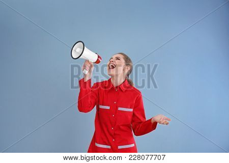 Young female emergency doctor shouting into megaphone on color background
