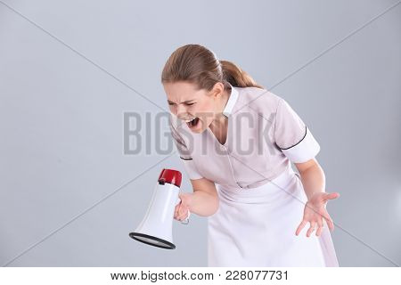 Young chambermaid shouting into megaphone on grey background