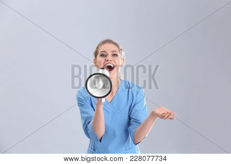 Young female doctor with megaphone on grey background