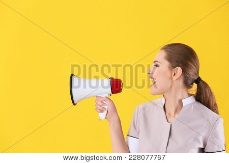 Young chambermaid with megaphone on color background